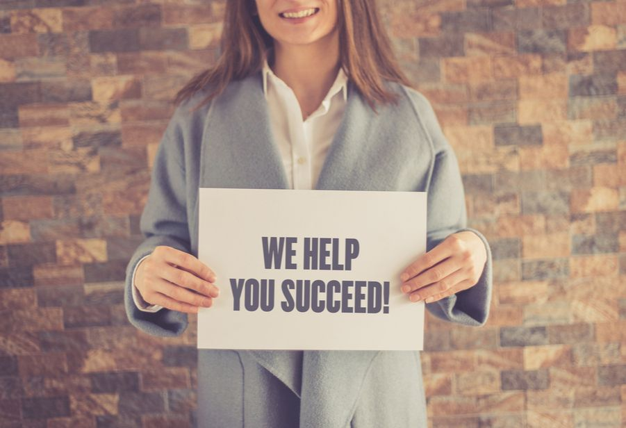 """Woman holding post with """"We help you succeed"""""""