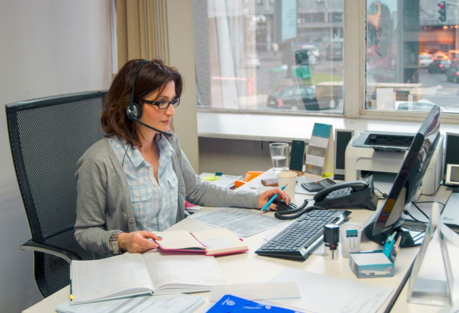 B2B Telemarketing campaign: business woman at her desk, making phone calls.