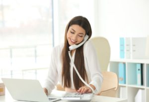 Young business woman with laptop and telephone